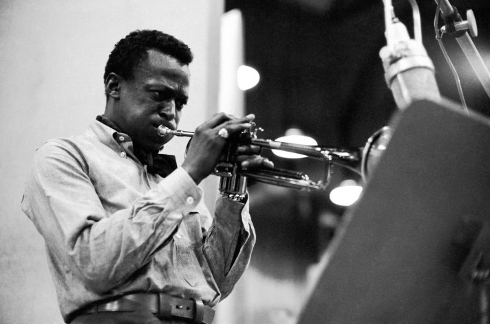 Miles Davis playing trumpet into microphone in studio